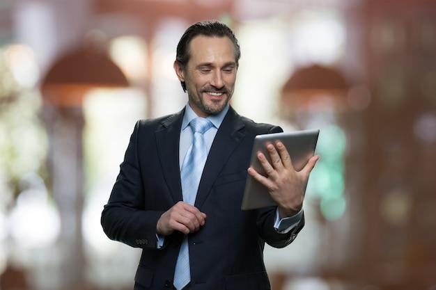 Homme d'affaires mature souriant regarde l'écran de la tablette. restaurant à l'intérieur sur le fond.