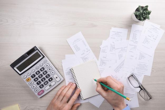 Homme d & # 39; affaires méconnaissable à l & # 39; aide de la calculatrice sur le bureau et l & # 39; écriture, prenez note avec calculer le coût au bureau à domicile. concept de comptabilité financière. taxes, achats, gestion des coûts.