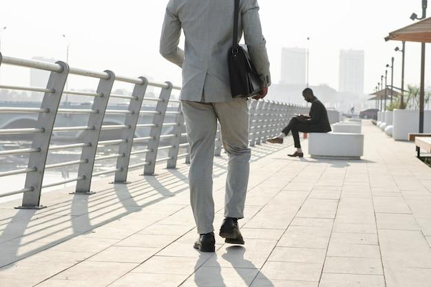 Homme d'affaires méconnaissable marchant le long de la rue