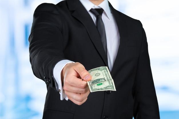 Homme d'affaires méconnaissable montre un billet de banque en dollars