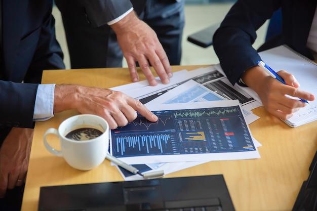 Homme d'affaires méconnaissable pointant sur un graphique imprimé et montrant un graphique à ses collègues. partenaires de contenu professionnels prenant des notes pour les statistiques. concept de coopération, communication et partenariat