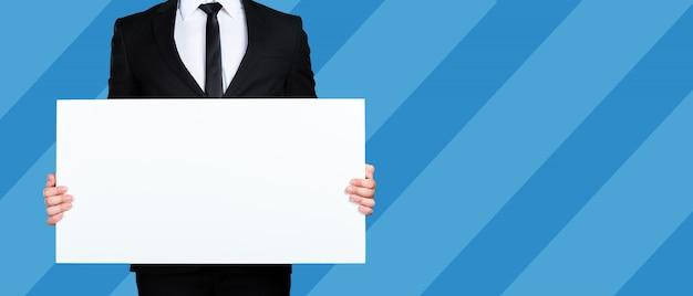 Homme d'affaires méconnaissable tenant un morceau de papier vierge ou une pancarte avec fond