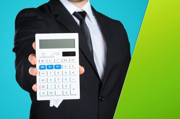 Homme d'affaires méconnaissable vous montrant une calculatrice.