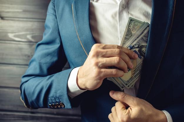 Homme d'affaires, membre ou officier met un pot-de-vin dans sa poche