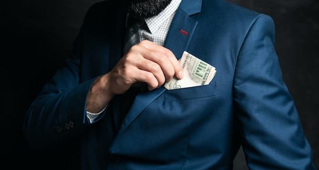 Homme d'affaires met de l'argent dans sa poche sur une surface sombre
