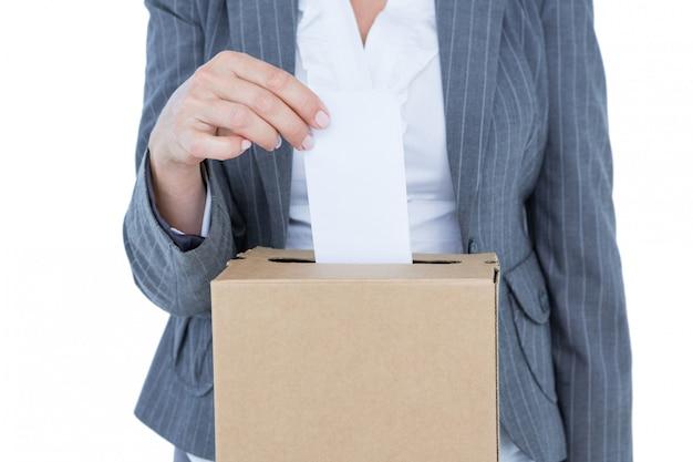Homme d'affaires mettant le bulletin de vote dans la boîte de vote