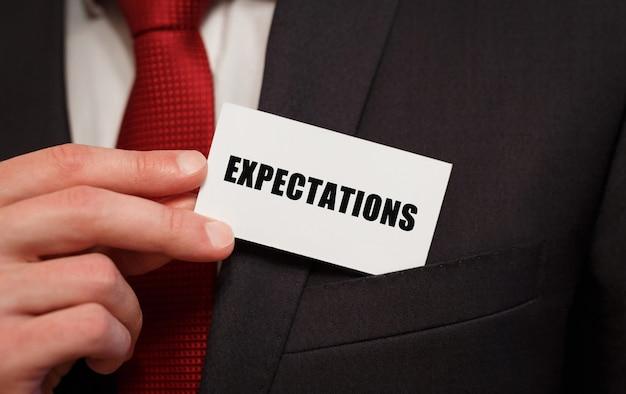 Homme d'affaires mettant une carte avec des attentes de texte dans la poche