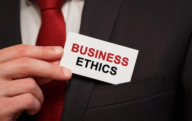 Homme d'affaires mettant une carte avec du texte d'éthique des affaires dans la poche