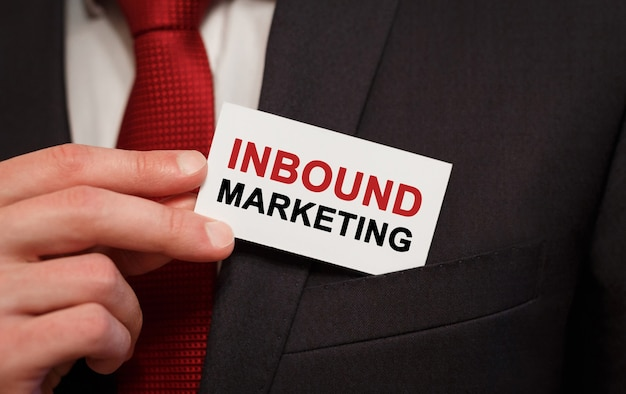 Homme d'affaires mettant une carte avec du texte inbound marketing dans la poche