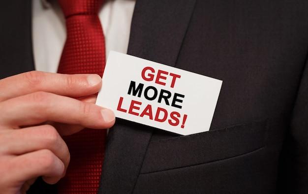 Homme d'affaires mettant une carte avec du texte obtenez plus de prospects dans la poche