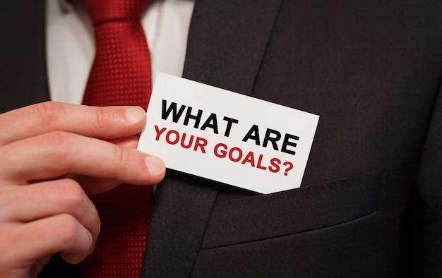 Homme d'affaires mettant une carte avec du texte quels sont vos objectifs dans la poche