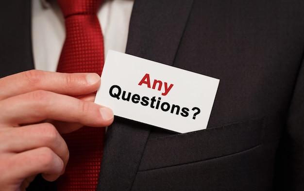 Homme d'affaires mettant une carte avec du texte toutes les questions dans la poche