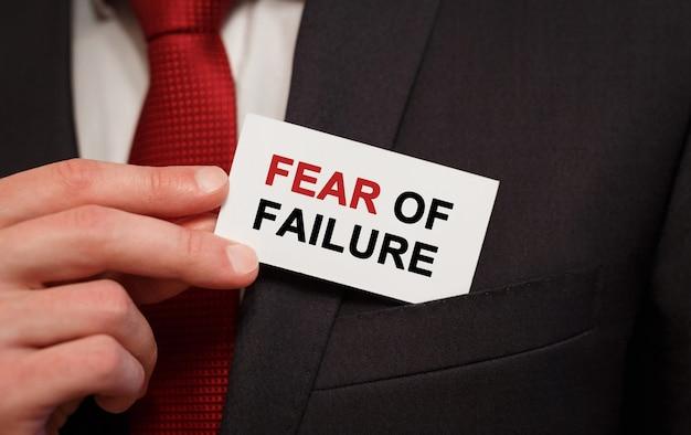 Homme d'affaires mettant une carte avec texte peur de l'échec dans la poche