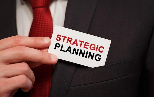 Homme d'affaires mettant une carte avec texte planification stratégique dans la poche