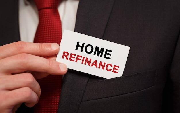 Homme d'affaires mettant une carte avec le texte de refinancement de la maison dans la poche