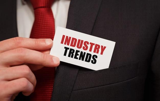 Homme d'affaires mettant une carte avec texte tendances de l'industrie dans la poche