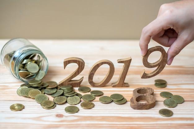 Homme d'affaires mettant le numéro «2019» en bois avec une pile de pièces d'or