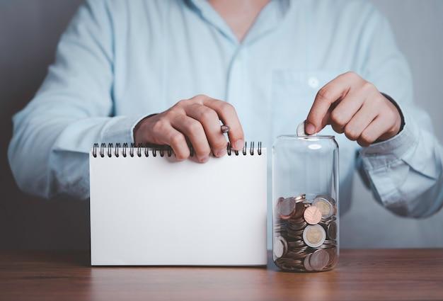Homme d'affaires mettant la pièce dans un pot d'économie d'argent avec une échelle virtuelle de montant de l'épargne pour l'avenir.