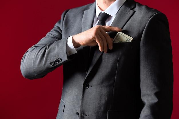 Homme d'affaires mettant un pot-de-vin dans la poche contre la couleur.