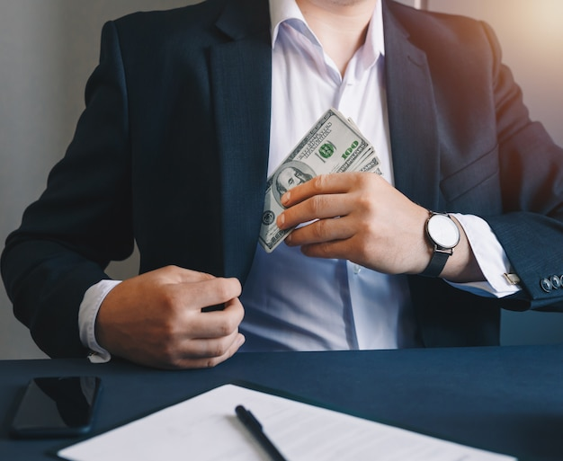 Homme affaires, mettre, billets banque, dollars, costume, poche