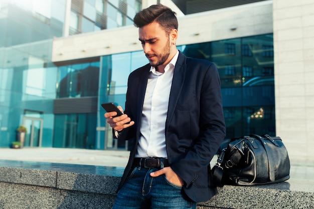 Homme d'affaires millénaire avec un téléphone portable dans ses mains