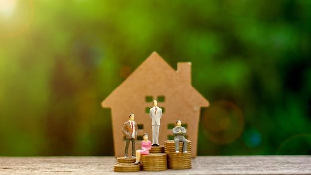 Homme d'affaires miniature assis sur des pièces d'or et un petit modèle de maison.