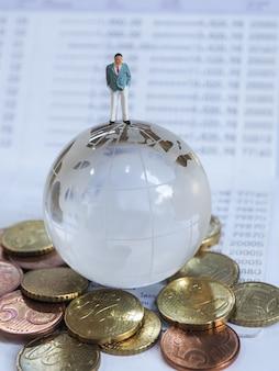 Homme d'affaires miniature debout sur un globe de verre, des pièces en euros et une banque de livres.