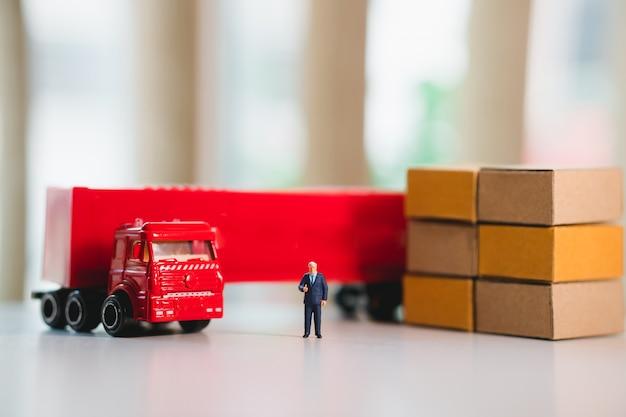 Homme d'affaires miniature debout près d'un camion rouge