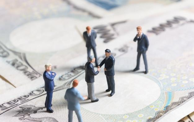 Homme d'affaires miniature debout et serrant la main sur les billets de banque japonais