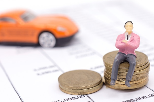 Homme d'affaires miniature et empiler des pièces sur le relevé et la voiture derrière. concept d'épargne et de prêt.