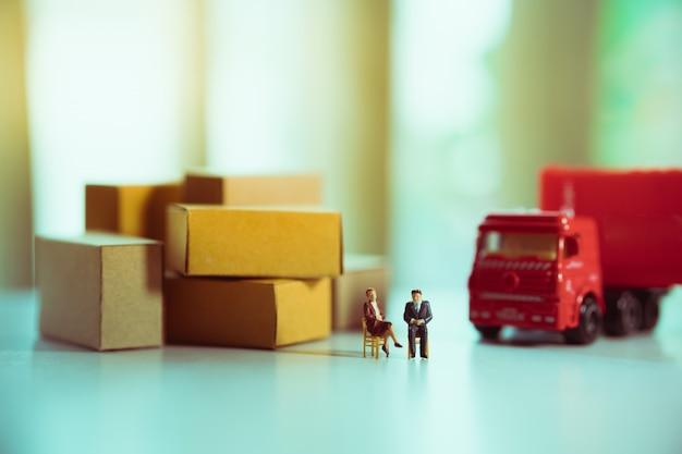 Homme d'affaires miniature et femme d'affaires avec un camion rouge