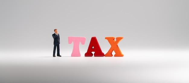 Homme d'affaires miniature figure en costume bleu foncé se tenant à côté du mot taxe en bois coloré