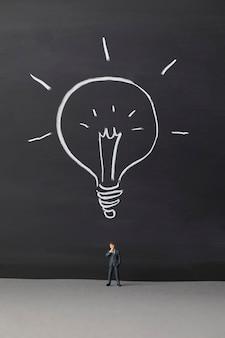 Homme d'affaires miniature avec une icône d'ampoule
