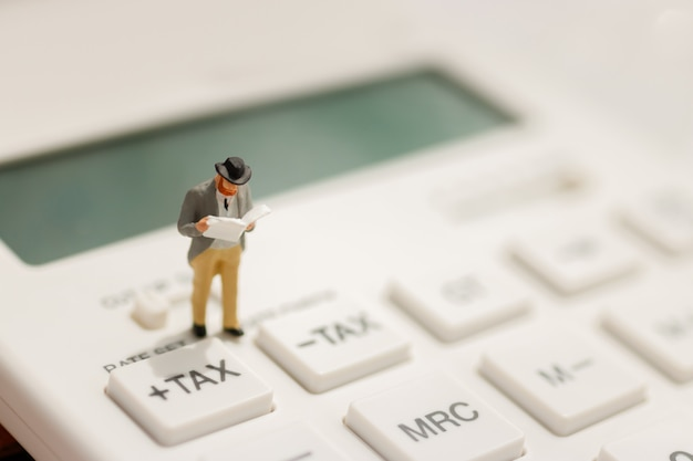 Homme d'affaires miniature stand lecture sur le bouton d'impôt de la calculatrice.