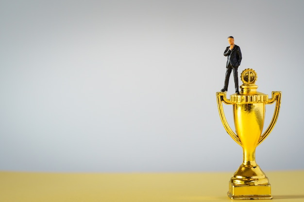 Homme d'affaires miniture sur trophées d'or sur une surface blanche