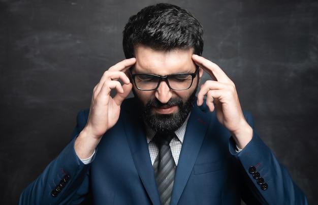 Homme d'affaires a mis ses doigts sur ses tempes et pense sur une surface sombre