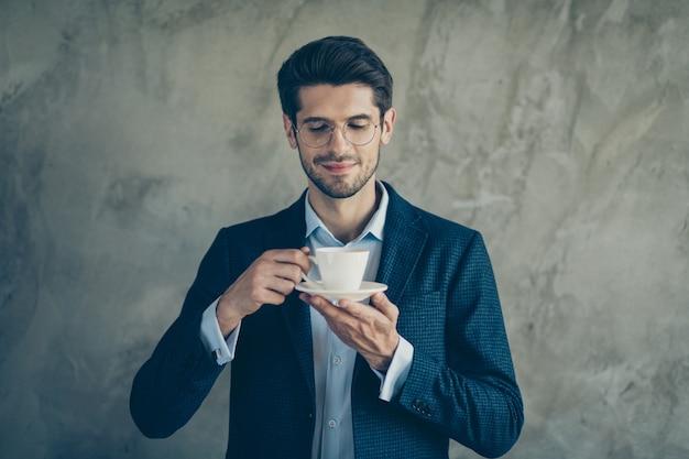 Homme d'affaires à la mode posant contre le mur gris