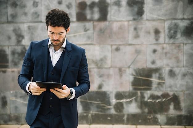 Homme d'affaires moderne à l'aide d'une tablette devant le mur