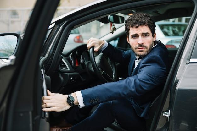 Homme d'affaires moderne assis dans la voiture