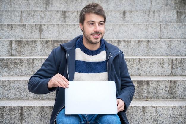 Homme d'affaires moderne beau hipster, utilisant un ordinateur portable dans la ville, avec une expression positive.