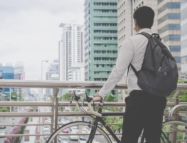L'homme d'affaires moderne fait du vélo à vélo pour éviter les embouteillages dans une ville occupée