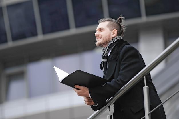 Un homme d'affaires moderne avec des papiers entre dans son bureau