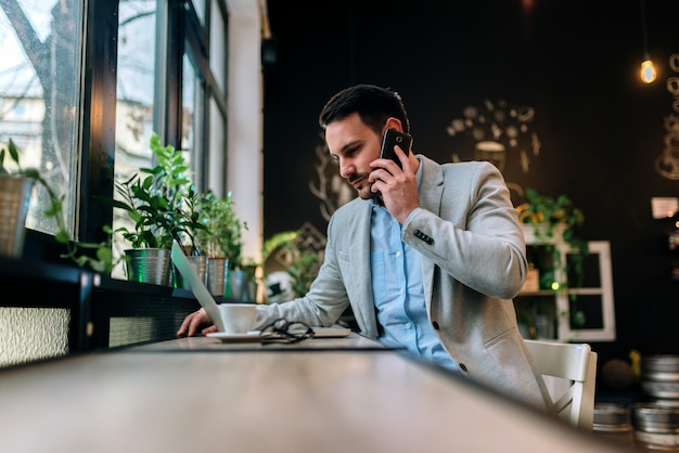 Homme d'affaires moderne parlant sur un smartphone alors qu'il travaillait sur un ordinateur portable dans le café.