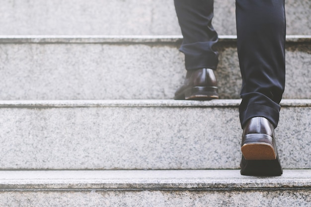 Homme d'affaires moderne travaillant les jambes de gros plan en montant les escaliers dans la ville moderne.