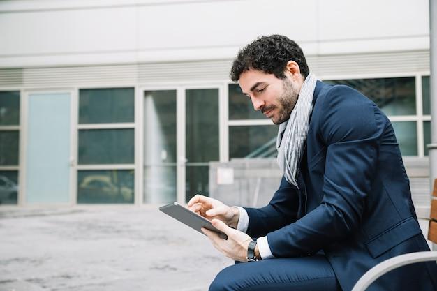 Homme d'affaires moderne utilisant un appareil à l'extérieur