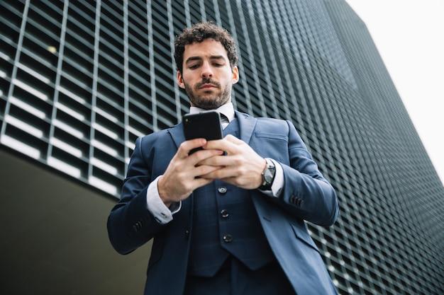 Homme d'affaires moderne utilisant un smartphone à l'extérieur