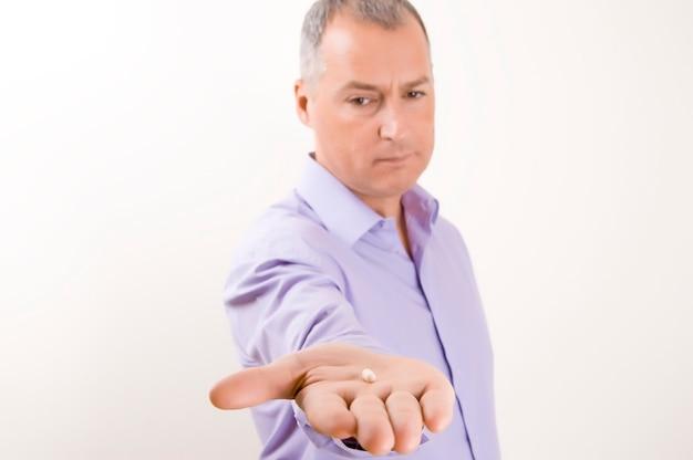 Homme d'affaires montrant une capsule. homme d'affaires aux cheveux gris tient une pilule sur blanc backgrou