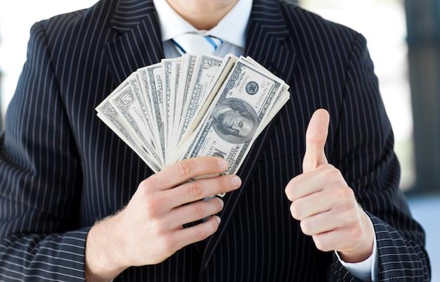 Homme d'affaires montrant des dollars avec les pouces vers le haut