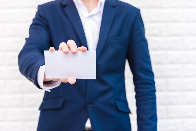 Homme d'affaires montrant du papier blanc