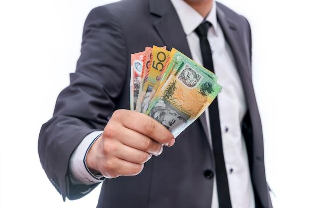 Homme d'affaires montrant fan de billets en dollars australiens